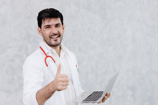 Happy doctor handsome male thumbs up good work with computer laptop.