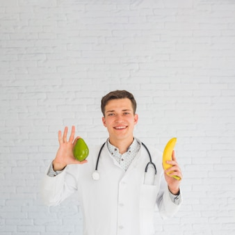 Happy doctor holding avocado and banana in hands