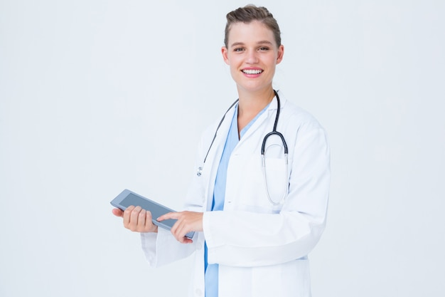 Happy doctor holding tablet pc
