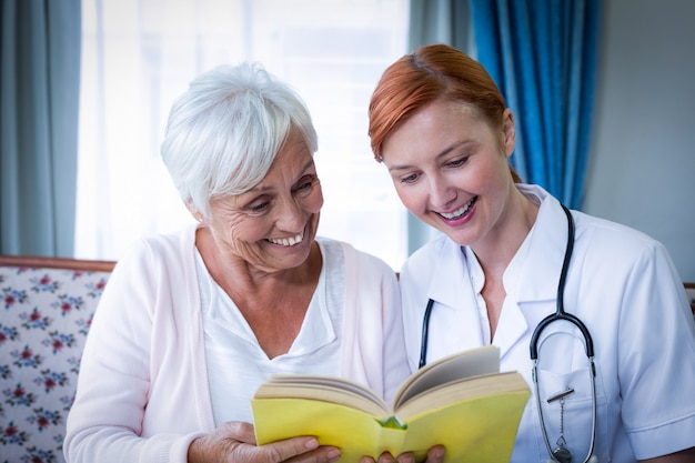 Happy doctor and patient reading a book