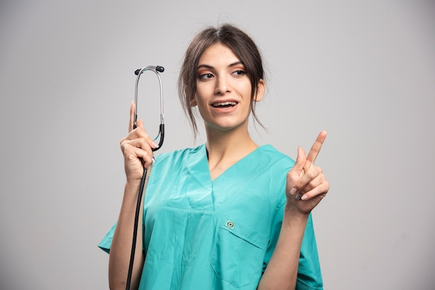 Medico felice che mostra stetoscopio su grigio