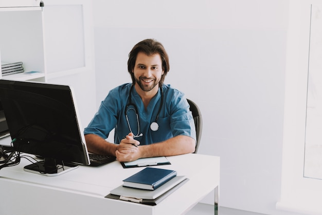 Happy doctor sitting at desk waiting for patient.