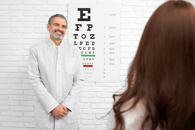 Happy doctor smiling, posing near eye chart in clinic.