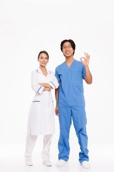 Счастливая пара врачей в униформе, стоя изолированной над белой стеной, показывая хорошо