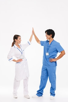 Happy doctors couple wearing uniform standing isolated over white wall, giving high five