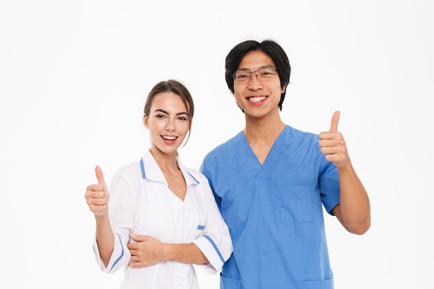Happy doctors couple wearing uniform standing isolated over white wall, showing thumbs up