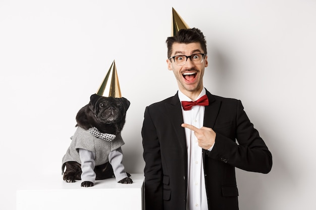 Happy dog owner and black pug wearing birthday party cones, man pointing at pug, standing over white.