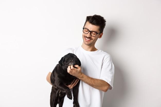 Счастливый владелец собаки, царапая лицо милого черного мопса и улыбаясь, погладить его животное, стоя на белом фоне.