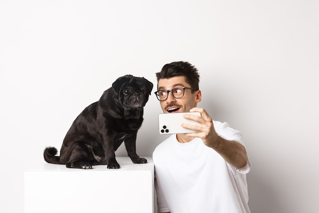 Счастливый владелец собаки, делающий селфи с милым черным мопсом, улыбаясь и с любовью глядя на собачку, держа мобильный телефон, белый фон.