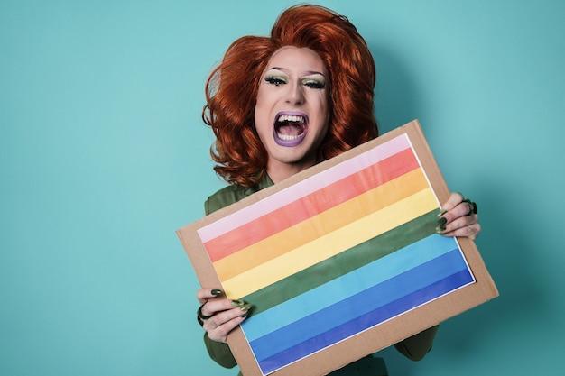 虹色の旗のバナーを保持している幸せなドラッグクイーン-lgbtの概念-顔に焦点を当てる