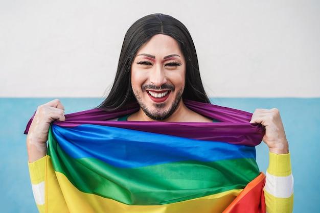 Счастливый трансвестит с радужным флагом лгбт - сосредоточьтесь на лице