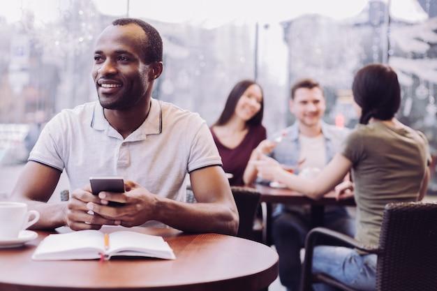 Счастливый мечтательный студент-мужчина с телефоном, сидя в кафе и глядя в сторону