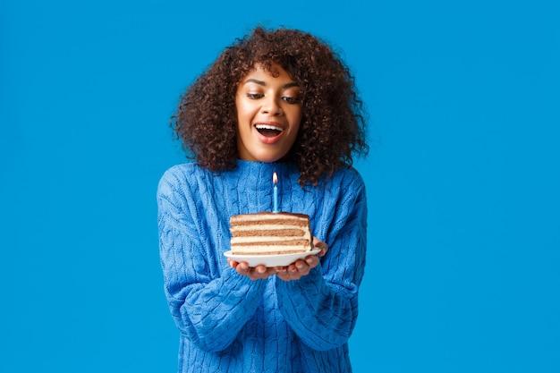 幸せな夢のような希望に満ちた誕生日の女の子が願い事をします。カーリーヘアカットの魅力的なアフリカ系アメリカ人女性、おいしいb-dayケーキ、立っている青い壁に火のともったろうそくを吹き消すために空気を吸い込みます。