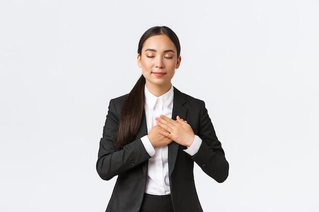 Счастливая мечтательная азиатская женщина-предприниматель в костюме закрывает глаза и, взявшись за руки, вспоминает прекрасные воспоминания, думая о чем-то приятном на белом фоне