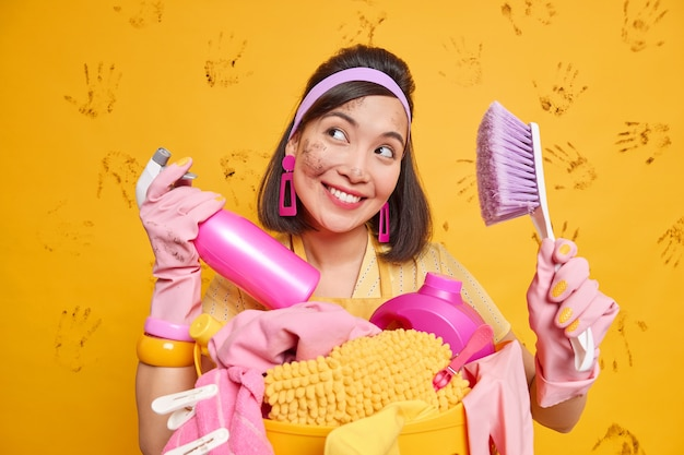 Happy dreamy asian housewife with untidy face smiles plasantly holds spray detergent and brush busy cleaning bathroom and doing laundry poses against yellow wall