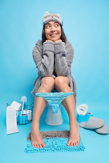 Happy dreamy asian woman wears grey blindfold and bathrobe lace panties down on legs feels relief while sitting on toilet bowl poses against blue wall in lavatory