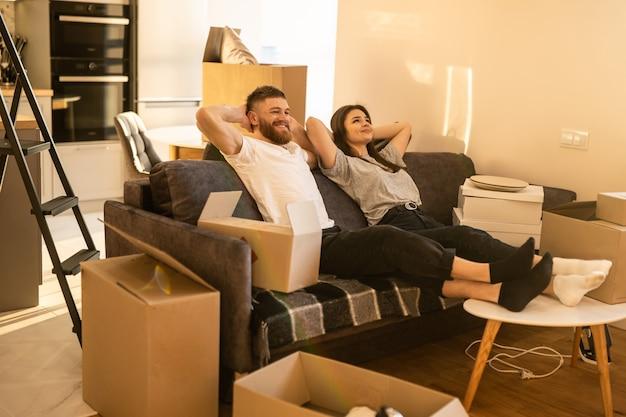 Счастливая мечтательная европейская пара, сидя на диване у себя дома. концепция переезда в новую квартиру. идея молодой семьи. картонные коробки с вещами. интерьер однокомнатной квартиры. солнечный день