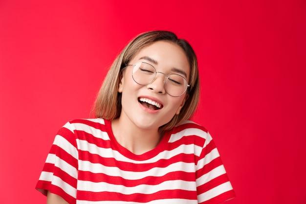 Happy dreamy glad asian girl feel stuffed good after eating favorite sandwich woman wear glasses clo...