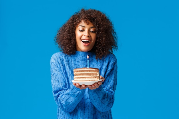 Happy dreamy and hopeful birthday girl making wish. attractive african american woman with curly haircut, inhale air to blow-out lit candle on tasty b-day cake, standing blue wall.