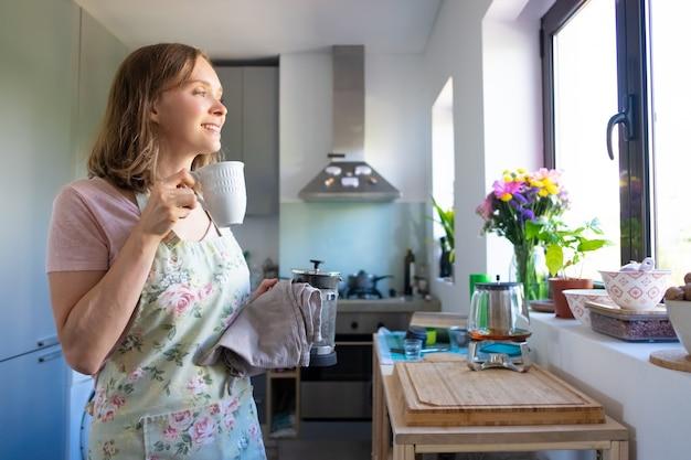 Casalinga sognante felice che indossa il grembiule, beve il tè e guarda fuori dalla finestra nella sua cucina. cucinare a casa e concetto di pausa tè