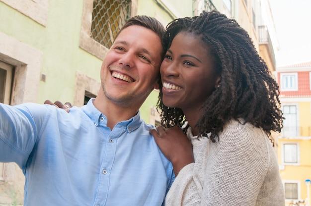 Happy dreamy intercultural couple enjoying romantic date in city