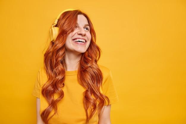 Счастливая мечтательная рыжая женщина широко улыбается, будучи в хорошем настроении, слушает музыку через беспроводные стереонаушники, носит простую футболку