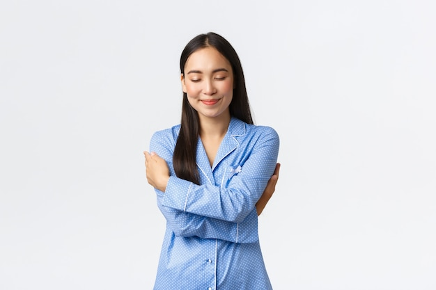 Happy dreamy tender asian girl in blue pajamas, close eyes and smiling as daydreaming, hugging herself, embracing own body in jammies, standing white background relaxed, daydreaming