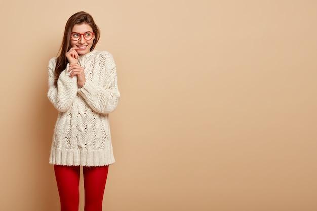 幸せな夢のような女性はまっすぐな髪をしていて、思慮深い表情で完全に嬉しそうに見え、人生の前向きな瞬間を想像し、白いジャンパー、赤いレギンスを着て、空きスペースのあるベージュの壁に隔離されています