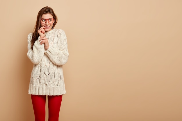Happy dreamy woman has straight hair, looks glad fully with thoughtful expression, imagines positive moment in life, wears white jumper, red leggings, isolated over beige wall with free space