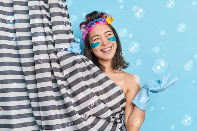 Happy dreamy woman thinks about something pleasant while taking shower raises hand in rubber glove undergoes skin and body care procedures