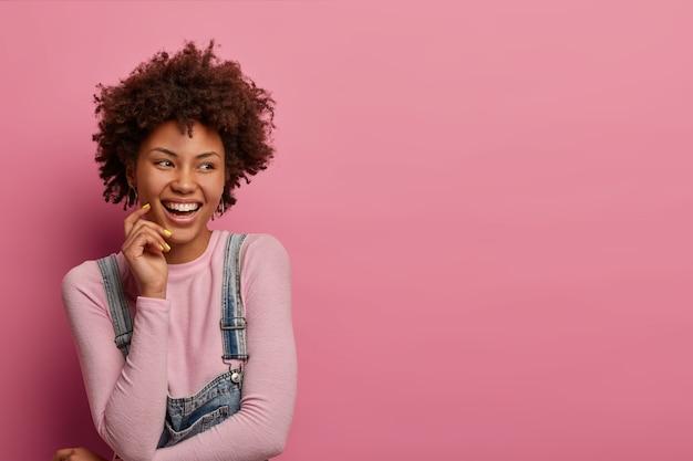 Felice donna sognante con acconciatura afro, è felice e gioiosa