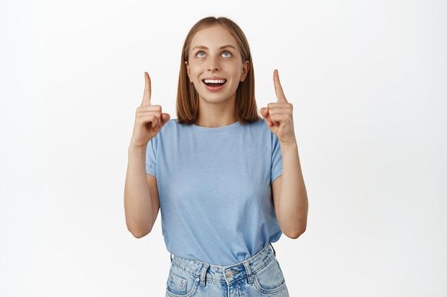 파란 눈을 가진 행복한 꿈꾸는 여자, 하얀 치아 미소, 손가락을 위로 가리키고 광고에 매료된 표정, 프로모션 제안 확인, 흰 벽 위에 파란색 티셔츠를 입고 서 있습니다.