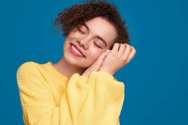 巻き毛の幸せな夢のような若い女性
