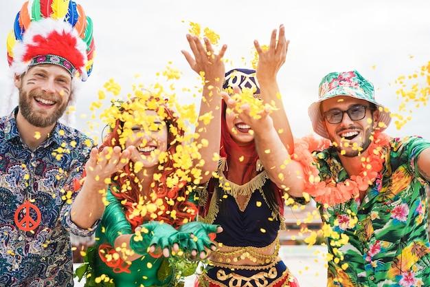 색종이를 던지는 카니발 파티에서 축하 행복한 옷을 입고 사람들