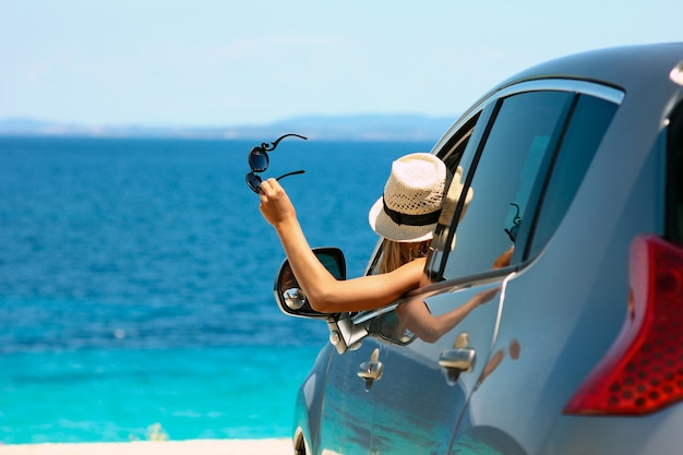 Happy driver girl in hat and sunglasses in car at sea in summer