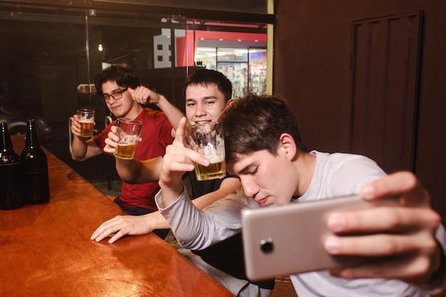 Счастливые пьяные друзья делают селфи, попивая пиво в баре.