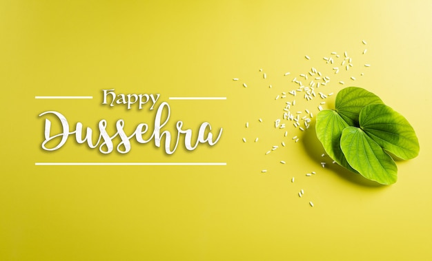 Happy dussehra concept. green leaf and rice on yellow pastel background