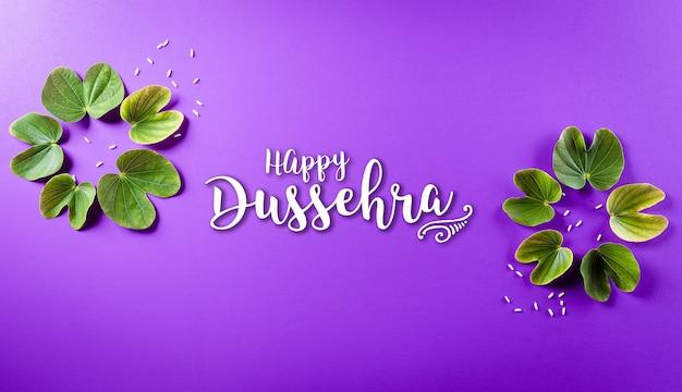 幸せなdussehra。緑の葉と紫のパステル背景の米