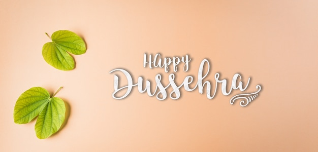 Happy dussehra, green leaf on orange pastel background.