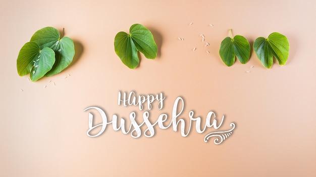 Happy dussehra. green leaf and rice on orange pastel background.