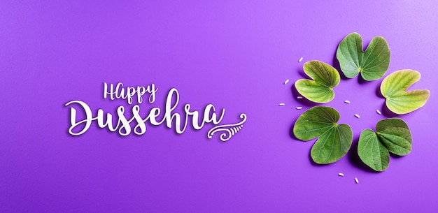Happy dussehra with green leaves on purple surface