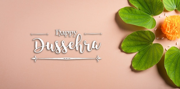 Happy dussehra. yellow flowers, green leaf and rice on orange pastel background