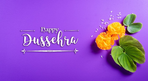 Happy dussehra. yellow flowers, green leaf and rice on purple pastel background