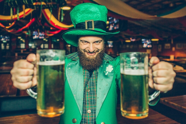 Happy and eacited young man in st. patrick's suit in pub alone. he hold two mugs of beer and look .