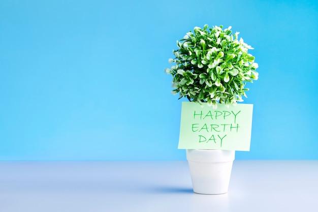 ハッピーアースデイバナー。青い背景に空白の緑の植物。