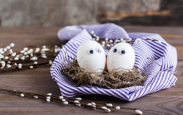 イースター、おめでとう。鳥の巣と木製のテーブルの柳の枝に目が付いている未着色の卵のカップル。
