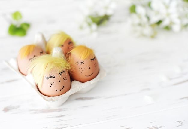 Христос воскрес. пара неокрашенных яиц с счастливым лицом и ветками вишнево-белый деревянный