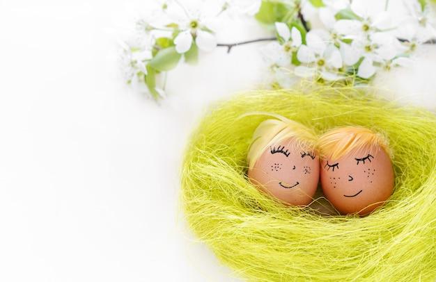イースター、おめでとう。コピースペース、バナーと白い背景の上の幸せそうな顔と着色されていない卵のカップル