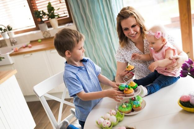イースター、おめでとう。イースターエッグを描いている母親と彼女の子供たち。イースターの準備をしている幸せな家族
