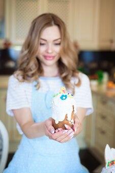 イースター、おめでとう。ケーキを手にしたお母さんがイースターの準備をしています。